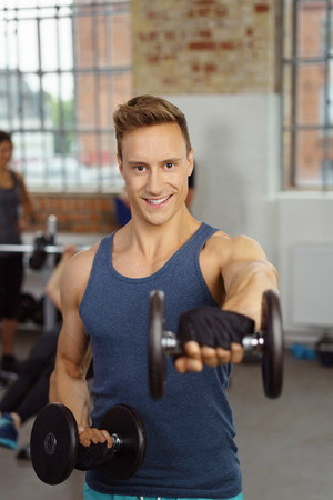 front raise: Single smiling young adult man in blue shirt performing front raise dumb bells exercises for shoulder conditioning at gym