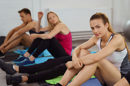 active adult community: Seated woman wraps her arms around knees and looks at camera while next to other athletes