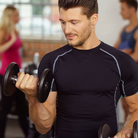 sport fitness: Fit muscular man working out with weights lifting a dumbbell in his hand to strengthen his biceps in a gym , close up cropped view Stock Photo
