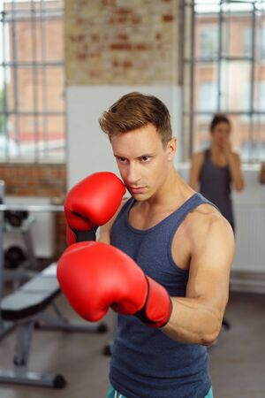 Handsome athlete in red boxing gloves in gym takes fighting stance as woman watches from nearby