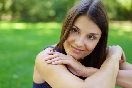 mujeres morenas: Primer plano de una sonrisa mujer joven en el pelo negro largo y vestido sin mangas azul con el espacio verde detrás de ella