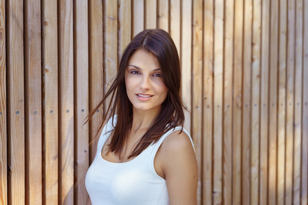adult wall: Gorgeous grinning single young adult woman in white sleeveless top and long brown hair beside wooden wall
