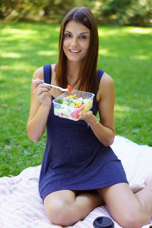 Young woman enjoying a healthy salad lunch as she sits relaxing on a rug on the grass in the park smiling at the camera