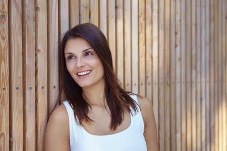 Smiling attractive single young adult woman in white sleeveless top and long brown hair leaning against wooden wall Stock Photo