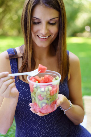 eating fruit: Healthy happy woman eating a fresh fruit salad from a plastic tub smiling in anticipation as she lifts a forkful of watermelon Foto de archivo