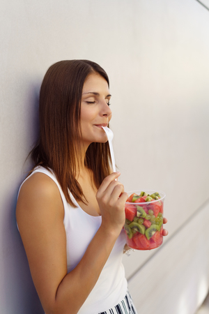 Young woman savoring a mouthful of fruit salad holding a tub on her hand and leaning back against a wall with her eyes closed in bliss and the fork to her mouth