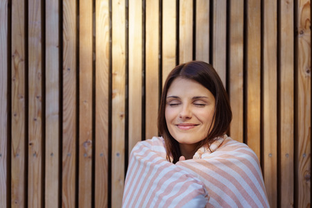 blissful: Blissful young woman after a spa treatment standing outside a wooden sauna wrapped in a towel smiling with closed eyes