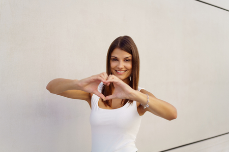 adult wall: Cute adult female making a heart symbol with hands while standing in front of blank wall outdoors Stock Photo