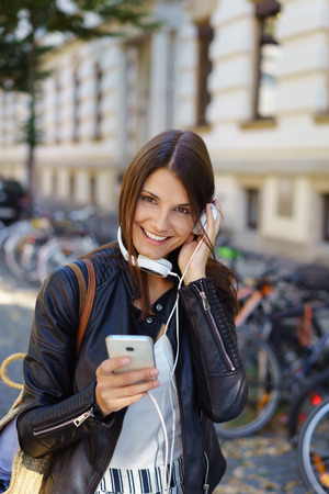 mp3 player: Young woman listening to headphones while standing outside in front of building with parked bicycles