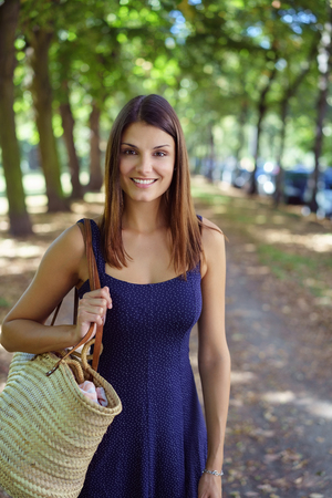 Pretty trendy young woman with a lovely smile walking down a tree-lined country lane with a fashionable bag over her shoulder Stock Photo