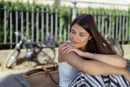 long brown hair: Wind blowing long brown hair of woman in sleeveless shirt and striped pants sitting outside Stock Photo