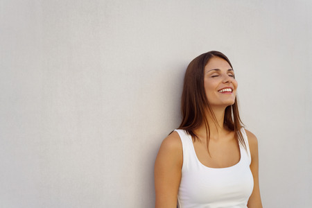 Woman with relieved expression and closed eyes leaning against blank white wall with copy space