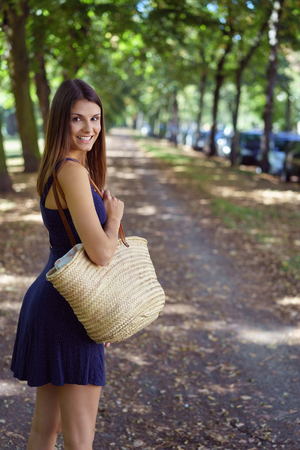 natural beauty: Attractive woman carrying a large trendy straw handbag turning back to smile at the camera as she walks down a leafy country lane