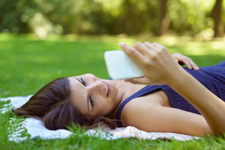 woman lying: Relaxed young woman lying on a rug on the grass in a park or garden smiling and reading her text messages on her mobile phone