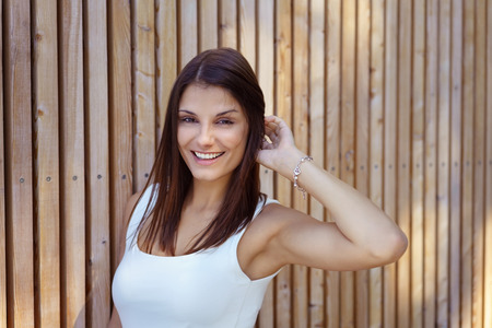 adult wall: Joyful grinning single adult woman in white sleeveless top and touching hair with hand beside wooden planked wall Stock Photo