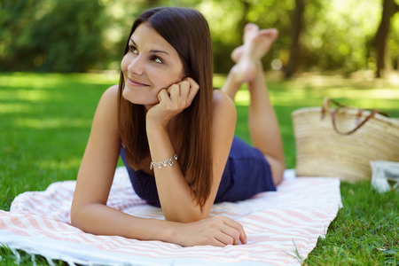 Grinning female adult wearing blue dress and fun expression while barefoot on blanket over grass outside in park during summer