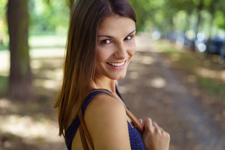 Caucasian woman: Attractive friendly young brunette woman turning to look back over her shoulder with a smile as she strolls down a country road, close up head and shoulders