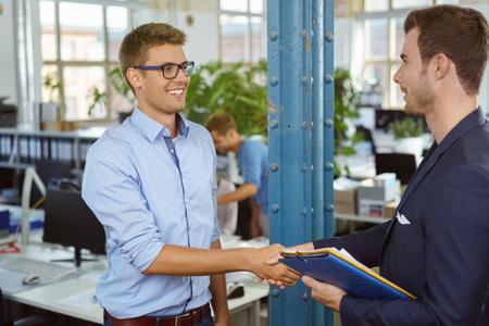 Uomo d'affari due agitando le mani su un accordo o un accordo con un sorriso felice mentre stanno in un ufficio open space con le persone in background