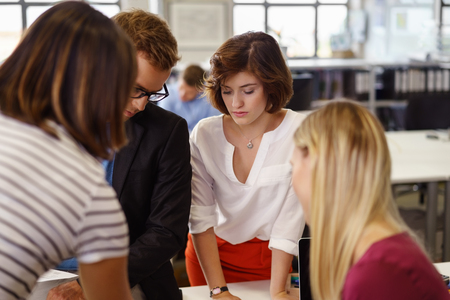 Young business team analysing a report standing grouped at a desk looking down reading with engrossed expressions with focus to an attractive woman Stock Photo