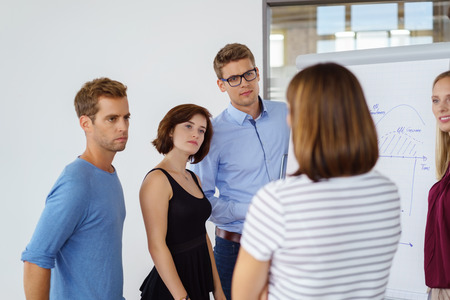 addressing: Manageress addressing a young business team of diverse people as they stand grouped around a flow chart listening with serious intent expressions