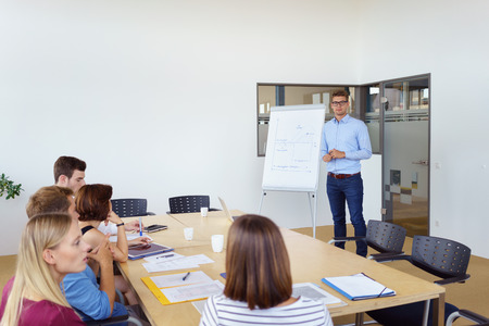 sit around: Businessman giving a lecture or presentation to colleagues in the office as they sit around a conference table