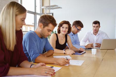 Grupo de jóvenes empresarios dedicados sentados en una mesa de conferencias en la oficina trabajando duro en el papeleo y tabletas con el foco a una mujer joven y sonriente mirando a la cámara