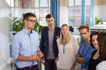 Serious white collar workers standing around white board during important meeting in small office Stock Photo