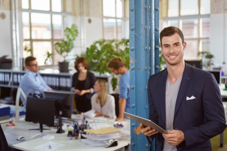working space: Confident businessman with a friendly smile standing leaning against a pole in the office holding his tablet computer as colleagues work behind him