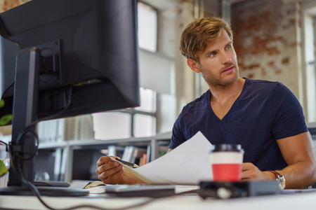 businessman pondering documents: Low angle view from behind the desktop monitor of a handsome young businessman working in an office holding a document and looking to the side with a thoughtful expression