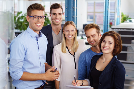 Group of five smiling and good looking male and female office workers standing together while taking notes about their schedule Фото со стока