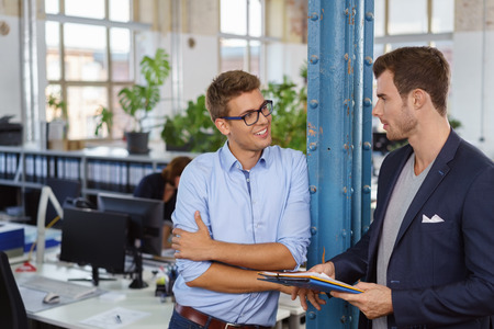 Two relaxed confident young businessmen having a discussion as the one leans against a support pole in the office listening with folded arms and a friendly smile Stock Photo