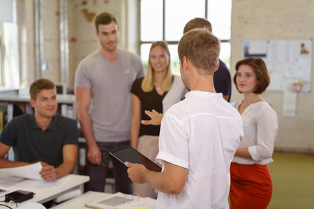 Team leader addressing his colleagues standing holding a tablet and gesturing as they stand grouped listening and watching, focus to his back Stock Photo