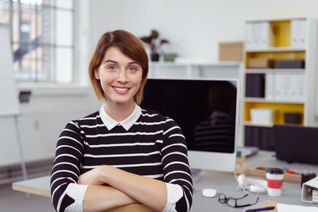Cute young single businesswoman or scholar in black and white striped shirt in office at desk
