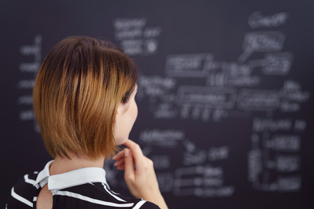 looking away: Businesswoman or teacher pondering a problem standing looking away from the camera at a blurred blackboard full of notes and calculations