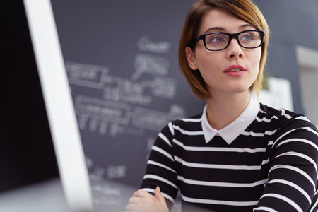 smartly: Smartly dressed office worker looks to one side while sitting at desk near chalk board Stock Photo
