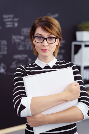 pert: Efficient business secretary or personal assistant holding an office binder clasped in her arms looking at the camera with a pert expression Stock Photo