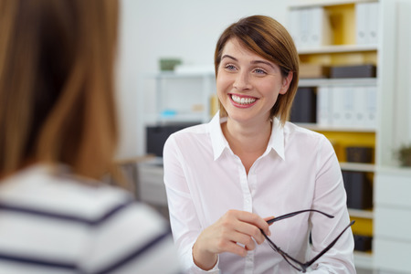 Woman holds her glasses in one hand while smiling at her associate as they talk in the office