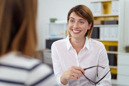 personas dialogando: Mujer sostiene sus gafas en una mano mientras sonríe a su asociado mientras hablan en la oficina
