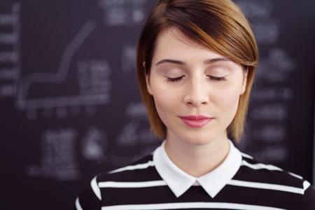 Serene giovane donna meditazione con gli occhi chiusi e un lieve sorriso di soddisfazione, close up testa e le spalle con lo spazio della copia