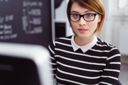 Vrouw met een bril en kort bruin haar werkt op de computer naast een schoolbord Stockfoto