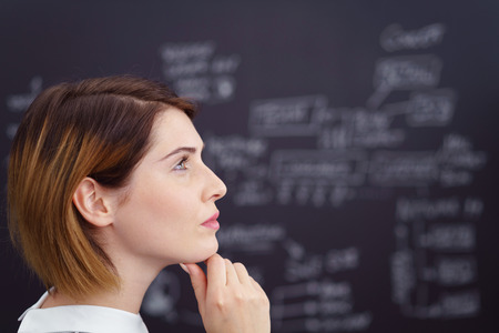 scholarly: Thoughtful young student or teacher standing in front of a blackboard with notes staring off to the side in profile with a contemplative expression, close up head shot Stock Photo