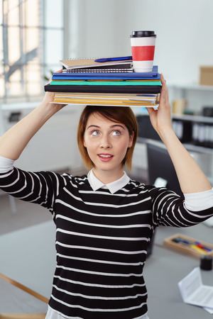 Young adult woman in black and white striped shirt holding notebooks and drink on head in small office Stock Photo