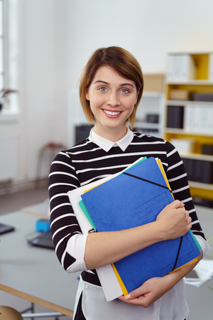 Single cheerful young adult woman in striped shirt holding blue, yellow, green and white folders in small indoor office