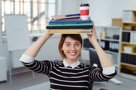 organise: Happy single young woman balancing notebooks and drink on head in small office with bookshelf in background Stock Photo