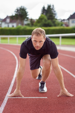 sports track: Muscular young male athlete in the starter position crouching down on an outdoors race track at a sports arena