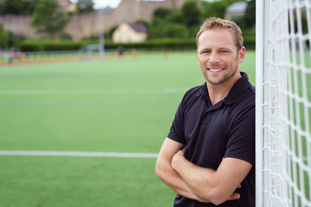 Relaxed happy football coach leaning on the goal posts with folded arms grinning at the camera, close up with copy space Stockfoto