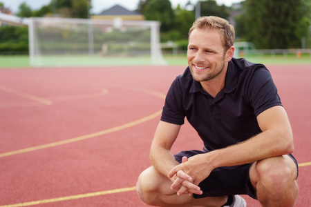 Happy attractive man squatting on a race track in a sports arena watching something off frame with a smile