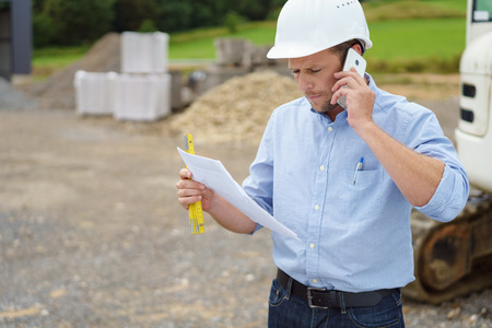 Architect or builder standing at a building site in his hardhat talking on a mobile phone as he reads a document in his hand Foto de archivo