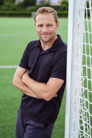 Smiling man leaning against the goalposts on an empty sport field with folded arms grinning at the camera
