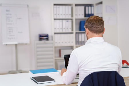 laptop computers: Rear view of a businessman working in the office sitting at a table with his laptop and tablet computers Stock Photo